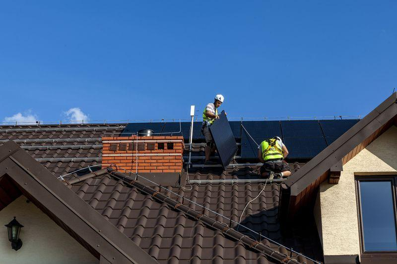 monterzy montujący panele fotowoltaiczne na dachu domu